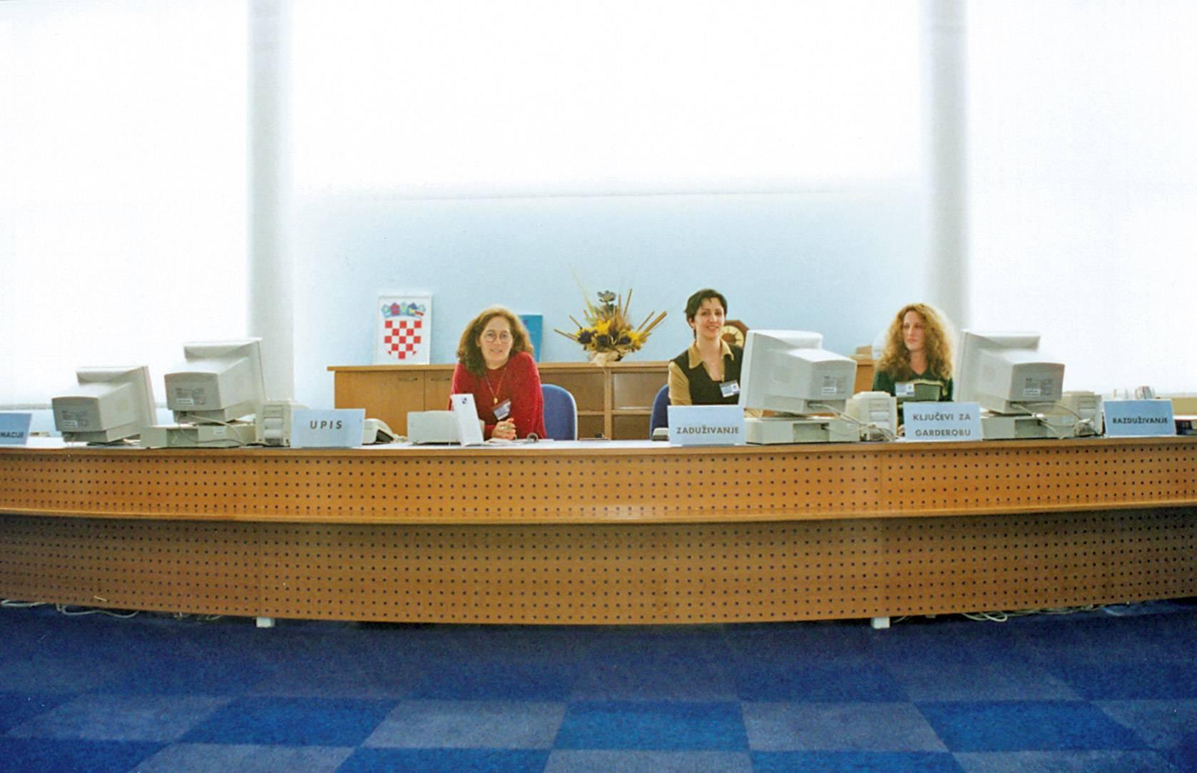 Knjižničarke Antonijela Nekić, Edita Bačić i Biserka Kulaš na pultu Knjižnice prvoga radnog dana prije probnog otvaranja Knjižnice 1. ožujka 1999.